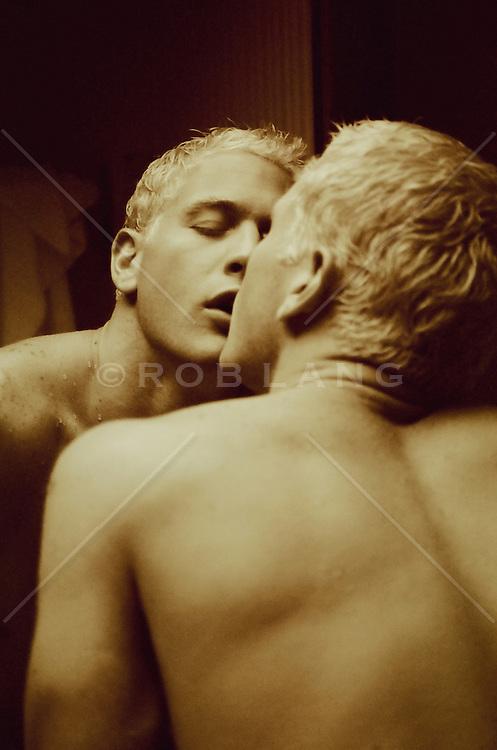 bleach blond man in a bathroom mirror kissing himself