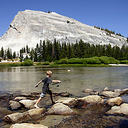 A young boy fishes Tuolumne River  with Lembert Dome looming above in Yosemite National Park. Model released.
