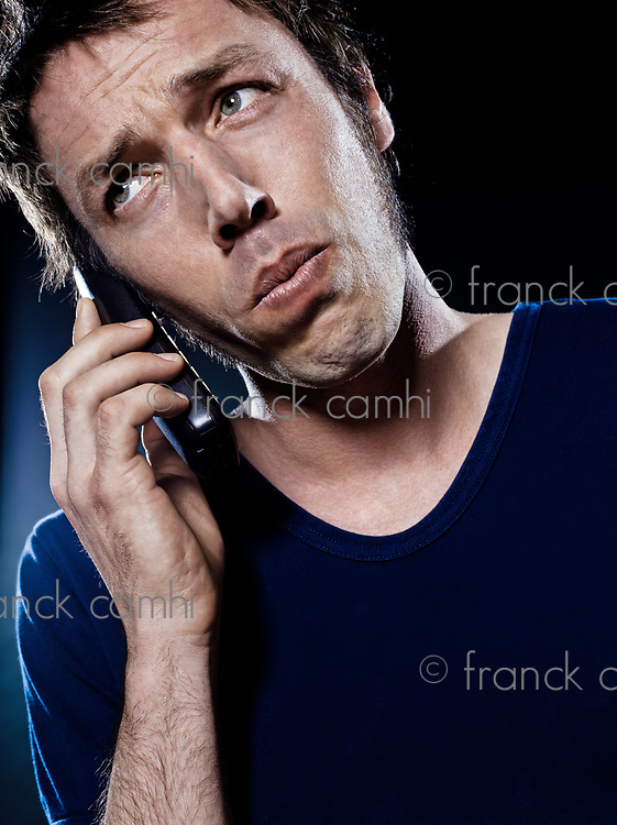 studio portrait on black background of a funny expressive caucasian man phoning worried
