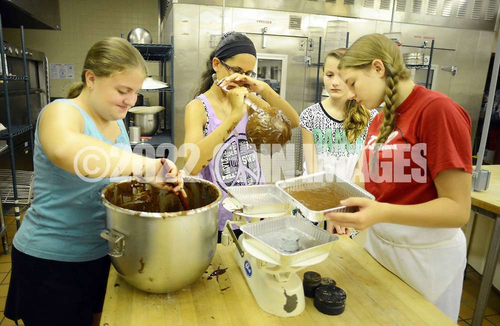From left, Rebecca Jeschonek. 13, Sarah Omietanski,14 Grace Carango, 11 and teaching assistant Christina Brambilla, 16 a tech school baking student work on a brownie recipe during baking class Wednesday July 20, 2015 at Bucks County Technical School in Fairless Hills, Pennsylvania. (Photo by William Thomas Cain)