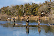 A novice fly fishermen practices witih his rod while his more experienced teacher and friend watches on the background.  Blue River in Tishomingo, Oklahoma.