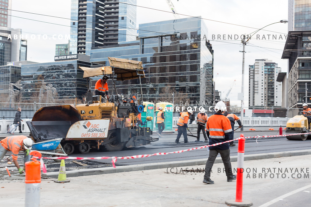 Road Construction workers in hi-vis clothing conduct roadworks as they lay down cement as they re-lay tram tracks Melbourne Victoria Australia