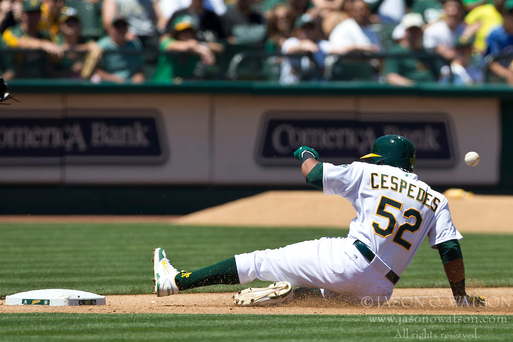 OAKLAND, CA - MAY 19: Yoenis Cespedes #52 of the Oakland Athletics slides into third base against the Kansas City Royals during the fourth inning at O.co Coliseum on May 19, 2013 in Oakland, California. The Oakland Athletics defeated the Kansas City Royals 4-3. (Photo by Jason O. Watson/Getty Images) *** Local Caption *** Yoenis Cespedes