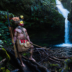 Huli wigmen with bow and arrow in front of a waterfall, Tari, Papoea New Guinea.