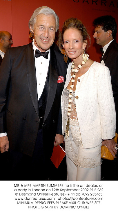 MR & MRS MARTIN SUMMERS at a party to celebrate the re-launch of Royal jewellers Garrard hosted by Jade Jagger and held at The Tower of London on 12th September 2002.