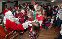 Santa Claus is surrounded by children as he passes out candy canes at the Wicwas Grange Christmas gathering with family and friends Saturday evening.   (Karen Bobotas/for the Laconia Daily Sun)