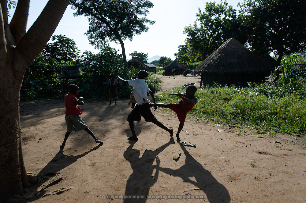 Three of Cecilia Amal's children—John Imoi Okello (left), Charles Okello and [UNKNOWN] play fight at their home in Imurok Payam in Eastern Equatoria, South Sudan on 9 August 2014.