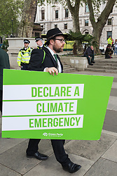 London, UK. 1st May, 2019. A Green Party activist among climate protesters attending a Declare A Climate Emergency Now demonstration in Parliament Square organised to coincide with a motion in the House of Commons to declare an environment and climate emergency tabled by Leader of the Opposition Jeremy Corbyn. The motion, which does not legally compel the Government to act, was passed without a vote.