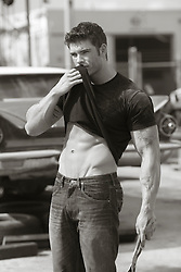 sexy auto mechanic lifting up his shirt to wipe his face while standing in an auto shop yard