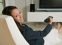 Woman reclining in living room Watching Television portrait