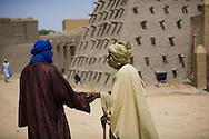 Two Tuareg men greeting in front of Sankore Mosque in Timbuktu, Mali.
