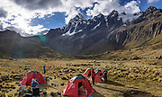 Day 2 of 10: The sun sets over the pass of Punta Union, seen from our tent camp in Huaripampa Valley at 13,780 ft or 4200 m, under Nevado Taulliraju (19,100 ft or 5830 m). Trek 10 days around Alpamayo in Huascaran National Park (UNESCO World Heritage Site), Cordillera Blanca, Andes Mountains, Peru, South America. This panorama was stitched from 3 overlapping photos.