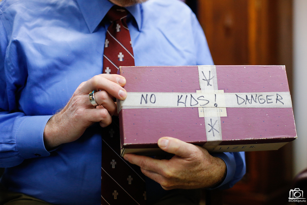 "Rev. Bruce Buchanan holds a shoebox with the label ""No Kids! Danger,"" during a gun buy-back in The Stewpot parking garage in Dallas, Texas, on January 19, 2013.  The shoebox was turned in with a handgun during a previous First Presbyterian Church of Dallas gun buy-back.  (Stan Olszewski/The Dallas Morning News)"