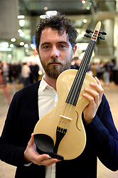 EDITORIAL USE ONLY Overall winner of the International Student Innovation Award Luca Alessandrini from Italy holds his violin, which uses the vibrating qualities of spiders silk, at this yearÕs International Student Innovation Awards at Central Saint Martins, London.