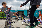 A young girl selects a bike at the Red Lantern Bike Shop in Braddock, Pennsylvania, USA on April 23, 2016.<br /> <br /> Brian Sink opened the Red Lantern Bike Shop opened in 2012 with the idea to provide bike repairs and free bikes for residents of Braddock. But after it became popular they lifted the restrictions on residence. Sink said he gave away about 1,100 bikes last year. <br /> <br /> Sink, known around town as &quot;The Bike Guy,&quot; fixes donated bicycles and gives them away for free at his shop that is housed in a shipping container and part of Gisle Fetterman's Free Store. The Free Store, receives surplus and donated clothing, school supplies, food and toys that are redistributed to people in need.