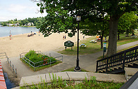 Picnic tables available in the shade for summer visitors to Endicott Rock Park at Weirs Beach.   (Karen Bobotas/for the Laconia Daily Sun)