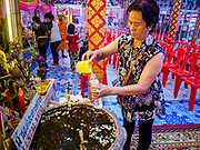 "29 MARCH 2017 - BANG KRUAI, NONTHABURI, THAILAND: A woman gets a bottle of ""lustral water"" (holy water) after a ""Resurrection Ceremony"" at Wat Ta Kien (also spelled Wat Tahkian), a Buddhist temple in the suburbs of Bangkok. People go to the temple to participate in a ""Resurrection Ceremony."" Groups of people meet and pray with the temple's Buddhist monks. Then they lie in coffins, the monks pull a pink sheet over them, symbolizing their ritualistic death. The sheet is then pulled back, and people sit up in the coffin, symbolizing their ritualist rebirth. The ceremony is supposed to expunge bad karma and bad luck from a person's life and also get people used to the idea of the inevitability of death. Most times, one person lays in one coffin, but there is family sized coffin that can accommodate up to six people. The temple has been doing the resurrection ceremonies for about nine years.          PHOTO BY JACK KURTZ"