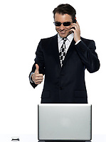 one criminal man computer hacker  caucasian computing on the phone happy satisfied in studio isolated on white background