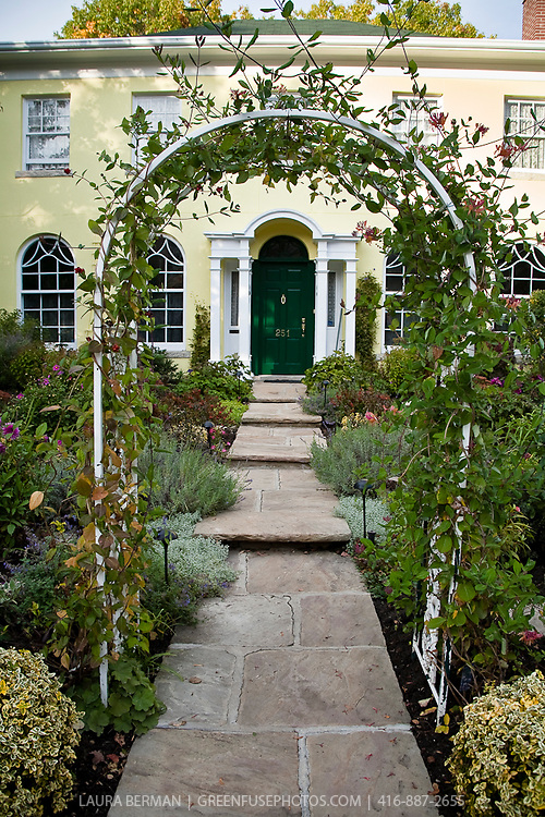 Wrought iron fence and white wrought iron arbor accentuate the flagstone path and front door of this distinctive yellow house.
