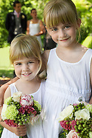 Two young girls embracing holding bouquets smiling