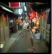 "Customers leave alleyway ""izakaya"", open air noodle and seafood restaurant/pubs on a steamy night, Shinjuku, Tokyo. Japan."