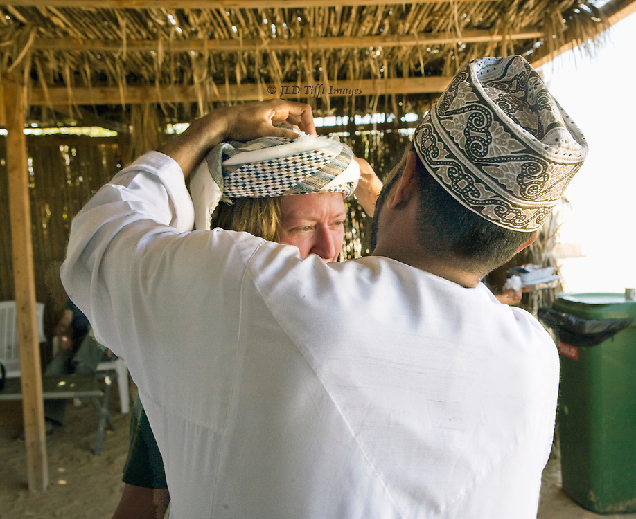 Omani man wraps a turban for an American woman tourist.  Her shy glance is seen over his left shoulder as he completes his demonstration of the technique.