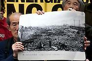"""Roma 16 Marzo 2011.Piazza della Rotonda al Pantheon.Manifestazione dei Verdi per denunciare la pericolosità delle scelte del Governo di un ritorno al nucleare in Italia.Partecipano all'iniziativa due cittadini giapponesi,Tsuboi Susumu di Hiroshima, 83 anni,  e Hiroshi Suenaga di Nagasaki, 75 anni. sopravvissuti alle bombe atomiche sganciate su Hiroshima e Nagasaki dagli americani alla fine della Seconda Guerra Mondiale. I due giapponesi stanno facendo il giro del mondo con la nave """"Peace Now""""  per dire no al nucleare. La foto di  Nagasaki dopo lo scoppio della bomba atomica mostrata dai due superstiti..Rome March 16, 2011.Al Pantheon Piazza della Rotonda.Demonstration of the Greens pointed out the dangerousness of the government's choice of a return to nuclear power in Italy. Participating two Japanese citizens of Hiroshima Susumu Tsuboi, 83 years, Hiroshi Suenaga and Nagasaki 75 years. survived the atomic bombs dropped on Hiroshima and Nagasaki by the Americans at the end of Second World War. The two Japanese are doing around the world with the ship """"Peace Now""""to say no to nuclear."""