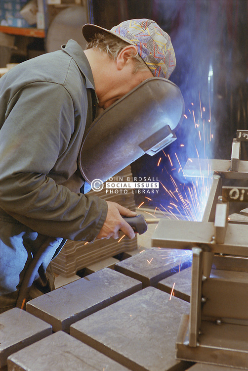 Man welding at engineering works wearing protective visor,