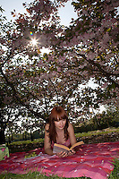 Young Woman Reading in Orchard