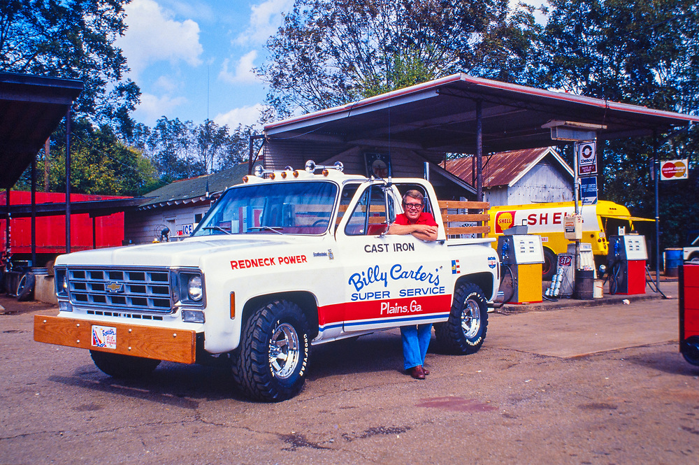"Billy Carter with his new ""Redneck Power"" pickup truck at his Plains, Georgia gas station. A nodel of the pickup was produced by Revell and sold internationally.  William Alton - Billy - Carter (March 29, 1937 – September 25, 1988) was an American farmer, businessman, brewer, and politician, and the younger brother of U.S. President Jimmy Carter. Carter promoted Billy Beer and was a candidate for mayor of Plains, Georgia. Carter was born in Plains, Georgia, to James Earl Carter Sr. and Lillian Gordy Carter. He was named after his paternal grandfather and great-grandfather, William Carter Sr. and William Archibald Carter Jr. respectively. He attended Emory University in Atlanta but did not complete a degree. He served four years in the United States Marine Corps, then returned to Plains to work with his brother in the family business of growing peanuts. In 1955, at the age of 18, he married Sybil Spires (b. 1939), also of Plains. They were the parents of six children: Kim, Jana, William ""Buddy"" Carter IV, Marle, Mandy, and Earl, who was 12 years old when his father died."