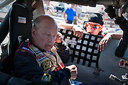 As a NASCAR race car throttle up to around 130 decibels, Charlie Imus, left, puts in hearing protection before his racing around the Stateline Speedway track.