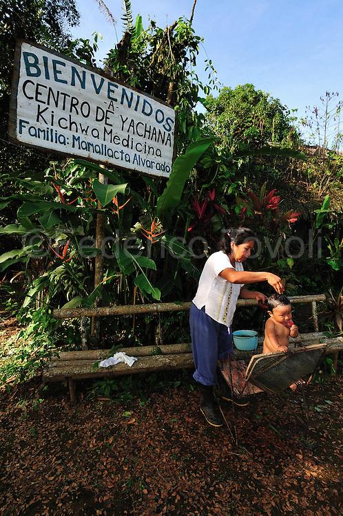 Flora Mamallacta giving a medical herbs bath to this son that suffering a bronchial disease