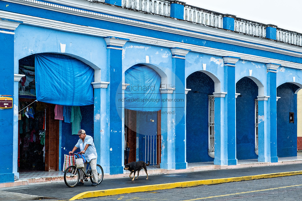 A man rides a bicycle past a brightly painted colonnaded style building along the Venustiano Carranza in Tlacotalpan, Veracruz, Mexico. The tiny town is painted a riot of colors and features well preserved colonial Caribbean architectural style dating from the mid-16th-century.