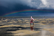 Under the arc of a rainbow, a woman heads out to gather shellfish at lowtide in Fumba, Zanzibar.