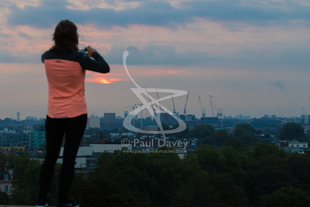 Primrose Hill, London, September 22nd 2016. A jogger stops to take a picture on Primrose Hill as the autumn equinox sun rises over London . ©Paul Davey<br /> FOR LICENCING CONTACT: Paul Davey +44 (0) 7966 016 296 paul@pauldaveycreative.co.uk