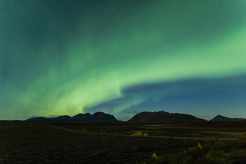 Aurora Borealis above the Denali Highway and the Alaska Range mountains at Landmark Gap in Interior Alaska. Autumn. Morning.