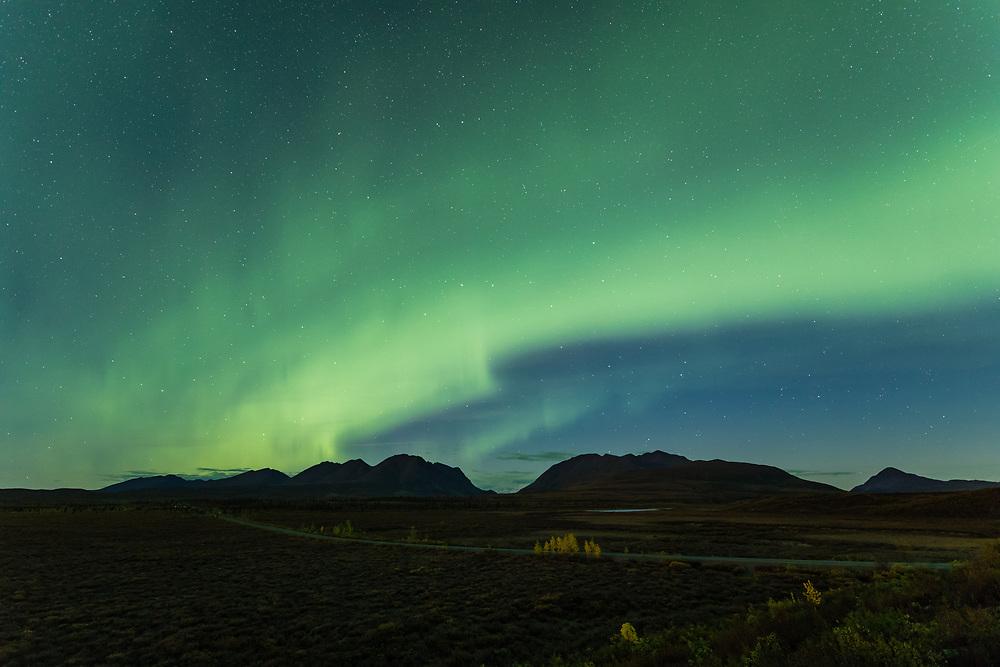 Aurora Borealis above the Denali Highway and the Alaska Range mountains at Landmark Gap in Interior Alaska. Autumn. Morning.