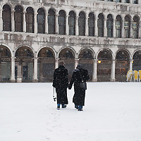 VENICE, ITALY - FEBRUARY 12:  Two men walk in the snow in St Mark's Square on February 12, 2012 in Venice, Italy. Italy, like most of Europe, is experiencing freezing temperatures, with the Venice Lagoon freeezing for the first time in over 20 years.