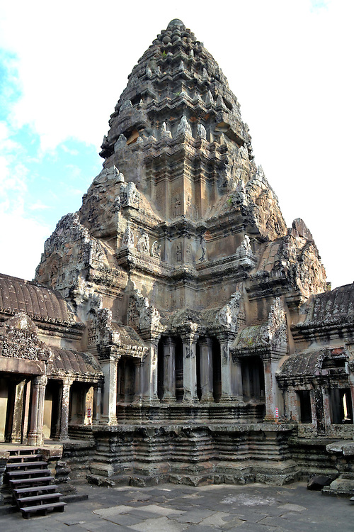 Central Tower at Angkor Wat in Angkor Archaeological Park, Cambodia<br /> Angkor Wat is shaped into a large rectangle. Inside are three galleries forming tiers. The levels are believed to represent the three highest levels of supremacy: the king, the moon and Vishnu. The temple also has four towers at the corners. The fifth prasat with a conical shape resembling a lotus bud is this central one. It reaches a height of 213 feet. These architectural elements are designed to symbolize Mount Meru. This arrangement is called a quincunx.