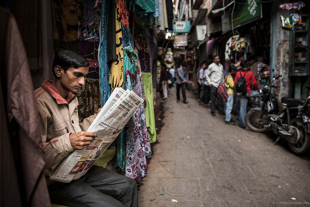 Man reading the newspaper in a Varanasi alley. India