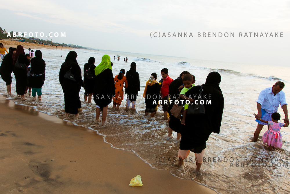 A group of Muslim women at the beach playing along the shoreline.Negombo is a major city in Sri Lanka, located on the west coast of the island and at the mouth of the Negombo Lagoon