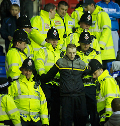 WIGAN, ENGLAND - Tuesday, March 16, 2010: A Wigan Athletic supporter is ejected from the stadium by police during the Premiership match at the DW Stadium. (Photo by David Rawcliffe/Propaganda)