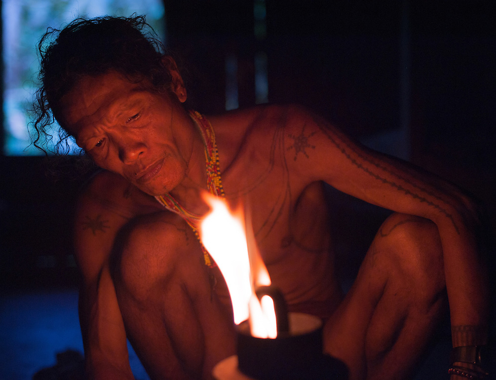 Mentawai indigenous man lightening a lamp (Indonesia).