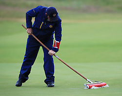 A member of ground staff sweeps the standing water on the green during day two of The Open Championship 2017 at Royal Birkdale Golf Club, Southport.