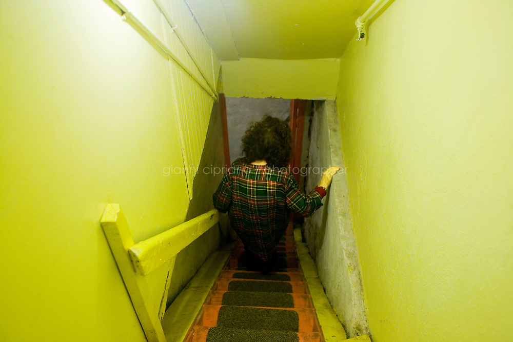 30 October, 2008. New York, NY. Cindy Worley walks down the stairs that lead to the root cellar, on the ground floor of her Harlem brownstone. Potatoes, butternut squashes, acorn squashes, onions and cabbage are momentarily stored in baskets, waiting for Cindy Worley to finish setting up the cellar. They would normally be store in sand or wooden cases. Cindy Worley grew up using root cellars and she now preserves fresh food produced either at the Joseph Daniel Wilson Memorial Garden in Harlem, or at the Community Supported Agriculture (CSA) farm in Upstate New York, which she is member of. The food she store is both consumed by her and her husband, and sold to support the Kitchen, a service provided by the Food Bank for New York City.   ©2008 Gianni Cipriano for The New York Times<br /> cell. +1 646 465 2168 (USA)<br /> cell. +1 328 567 7923 (Italy)<br /> gianni@giannicipriano.com<br /> www.giannicipriano.com