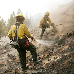 Firefighters Nick Stone (right back, from Boise) and Matthew Younger (middle front, from Emmett), work to suppress hotspots near Dog Mountain in Pine, Idaho while fighting the Elk fire. The Elk fire had burned 111,977 acres and was 10% contained as of 8am.  Wednesday August 14, 2013
