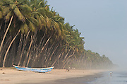 Fishing boat and palm trees. Beach at Beyin, Western Ghana.