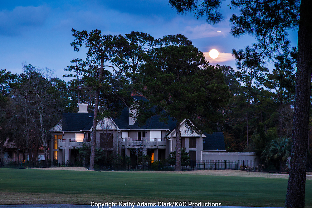 Full moon rising behind house on golf course in The Woodlands, Texas.
