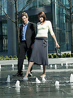 Mid-adult couple walking between water jets of fountain