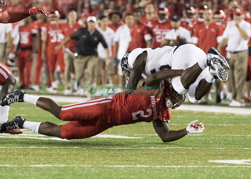 September 16, 2017 - Houston, TX, USA - Rice Owls running back Nahshon Ellerbe (25) is upended by Houston Cougars safety Khalil Williams (2) during the first quarter of the college football game between the Houston Cougars and the Rice Owls at TDECU Stadium in Houston, Texas. (Credit Image: © Scott W. Coleman via ZUMA Wire)